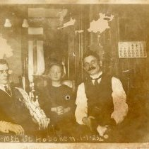 "Image of Sepia-toned photo of 2 men and a boy in parlor at 108 Tenth Street, Hoboken, January 1, 1923. 4-3/8"" wide x ca. 3-5/16"" high print. - Print, Photographic"