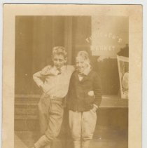 Image of Sepia-toned photo of two young boys outside entrance to Futterer's Market, 1001 Bloomfield St., Hoboken, no date, ca. 1924-1926. - Print, Photographic