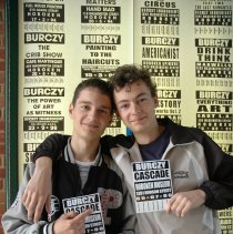 Image of Color photo of two boys posed with Burczy exhibit postcard in front of museum display case, Hoboken, May 21, 2006. - Photograph