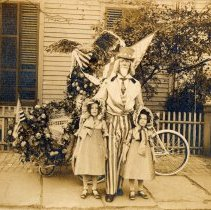 Image of Sepia-tone photo of a person in Uncle Sam costume with two costumed girls, no place, no date, ca. 1912-1925. - Print, Photographic