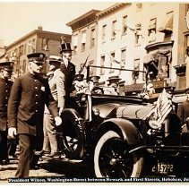 Image of Sepia-tone photo of President Woodrow Wilson in motorcade on Washington St. between Newark & First Sts., Hoboken, July 8, 1919. - Print, Photographic