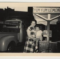 Image of Digital image of b+w photo of a Aunt Rose holding a young child near a Yum Yum cart with truck, 416 Clinton St., Hoboken, n.d., ca. 1950s. - Print, Photographic