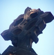 Image of 20: stone cross on roof above main entrance, east facade