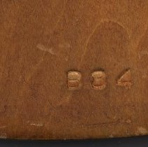 Image of detail back bottom: blind stamped numbers