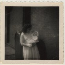 Image of photo 2: Polly (Mrs. Anton) Peskens  holding a baby