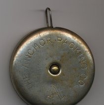 Image of side with custom engraving: Anchor Packing Co.; stop button at center