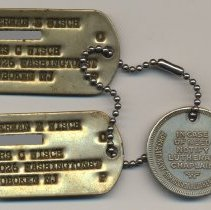 Image of dog (mililtary identification) tags with numbers masked