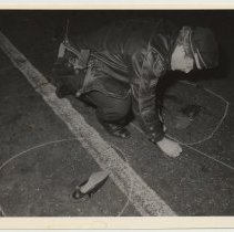 Image of B+W photo of Hoboken police officer marking a crime or accident scene, Washington St., Hoboken, n.d, ca. 1983-1988. - Print, Photographic