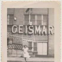Image of B+W photo of girl playing in 200 block of Bloomfield St. near back facade of Geismar's, Hoboken, n.d., ca. 1950s. - Print, Photographic