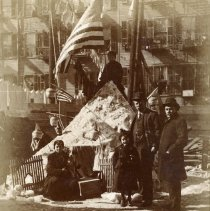 Image of Sepia-tone photo of snow fort with 3 children in backyard, American flags, Hoboken?, n.d., ca. 1912-1918. - Print, Photographic