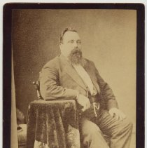 Image of Cabinet photo of a heavy man posed in photographer's studio, Hoboken, n.d., ca. 1880s. - Print, Photographic