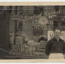 Image of B&W photo of John Schisano in front of Central Market, 161 14th St., Hoboken, n.d., ca. late 1940s or 1950s - Photograph