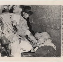 Image of B+W photo of physician treating an unconcious fireman at Holland Tunnel after explosion, May 13, 1949. - Print, Photographic