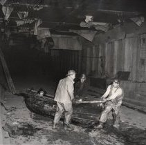Image of B+W photo of 3 sandhogs moving rowboat inside third tube of Lincoln Tunnel, Jan. 25, 1956. - Print, Photographic