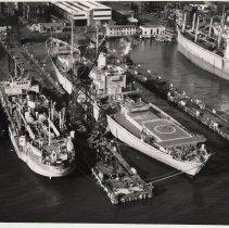 Image of B+W aerial photo of S.S. Ezra Sensibar & U.S.S. Compass Island at Bethlehem Steel Hoboken Shipyard, n.d., ca. 1969. - Print, Photographic