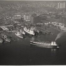 Image of B+W aerial photo of S.S. Houston, Seatrain Lines, approaching dock; USS Compass Island, USNS Vanguard & other ships at Bethlehem Steel Hoboken Shipyard, n.d., ca. 1969. - Print, Photographic