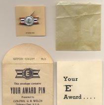 Image of pin with original glassine sleeve, envelope, information folder
