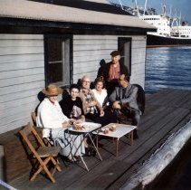 Image of Color photograph of a group seated on the floating shack docked at 4th St. & Hudson River, Hoboken, n.d., ca.1970s. - Photograph