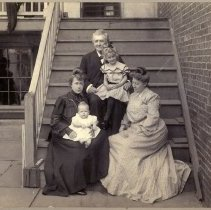 Image of Sepia-tone group photo of family posed on outside on back steps, Hoboken?, no date, circa 1895-1905. - Print, Photographic