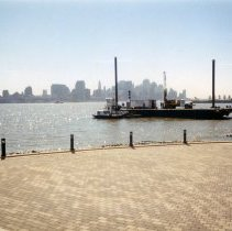 Image of Color photo of view southeast from Frank Sinatra Park amphitheather of barge & small boat, Hoboken, n.d., ca. 2002-2004. - Print, Photographic