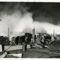 Image of B+W photos, 2, of firemen fighting fire at lumber yard at 11th to 12 Sts. & Hudson River, Hoboken, June 17, 1937. - Print, Photographic
