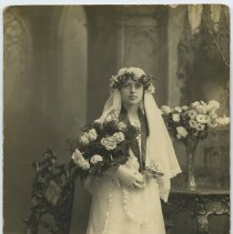 Image of Sepia-tone photo of girl with flowers, catechism, rosary posed in studio with religious interior backdrop, Hoboken, n.d., ca. 1910-1924 - Print, Photographic