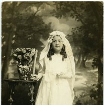 Image of Sepia-tone photo of girl with candle, catechism and rosary posed in studio, Hoboken, n.d., ca. 1918-1930. - Print, Photographic