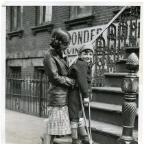 Image of B+W photo of Paul Crone on crutch being assisted up front stairs by sister Constance, street address not known, Hoboken, March 27, 1935. - Print, Photographic
