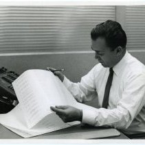 Image of B+W photo of Peter (Alvin P.) Roland working at a desk, Hoboken, n.d., ca. 1960-1970. - Print, Photographic