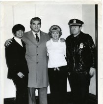 Image of B+W photo of (from left) Marian Roland; Peter Roland; woman; policeman, City Hall(?), Hoboken, n.d., ca. 1965-1975.  - Print, Photographic