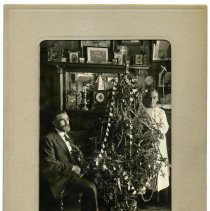 Image of Sepia-tone photo of man (Anthon Van Der Weil?) & woman (wife?) in parlor with Christmas tree, probably Hoboken, N.J., ca. 1920 or earlier. - Print, Photographic