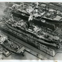 Image of B+W aerial photo of British ships being outfitted with armor at Bethlehem Steel shipyard, Hoboken, Apr. 25, 1940. - Print, Photographic