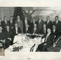 Image of B+W photo of R. Neumann & Co. executives posed at a holiday luncheon or dinner, n.p., December 1968. - Print, Photographic