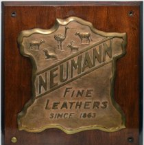 Image of Bronze plaque [company logo]: Neumann Fine Leathers Since 1863. N.d., ca. 1930-1960.