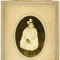 Image of Sepia tone photo of a young girl in white dress holding flower, Hoboken, n.d., ca. 1915-1925.