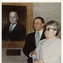 Image of Color photo of Dolly Sinatra with son, Frank Sinatra, in front of painted portrait of Martin Sinatra, n.p. (possibly Cathedral City, CA), n.d., ca. 1969-1970.  - Print, Photographic