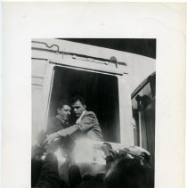 Image of Black-and-white photograph Frank Sinatra at rail passenger car door signing autographs for fans on the platform, n.p., n.d., ca. 1943-1947. Fan club copy. - Print, Photographic