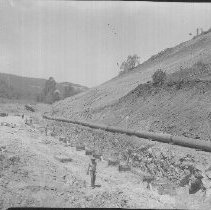 Image of 2013.2.242 - Man walks near pipes at Conn Dam Project