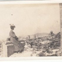 Image of 2015.39.20 - Woman sitting on the ruins of a building