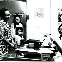 Image of Lois Hofstra admitting a young patient being accompanied by his family.