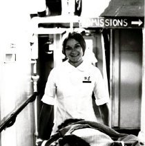 Image of Kathy Rheingans taking a patient to a local ward.