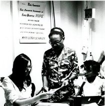 Image of Lois Hofstra, secretary, admits a young patient to ship's hospital