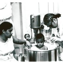 Image of Sister Theiophane Mandrogos with patient and parent.
