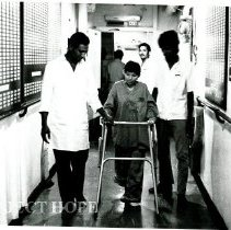 Image of A young lady being assisted in the corridor.  See Voyage boards on walls.