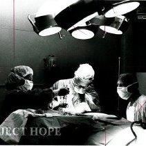 Image of Dr. Bert Wasserman in operating room accompanied by HOPE nurses.