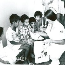 Image of Miss Nancy Hitt (HOPE pediatric nurse) presenting gifts to yourng Brazilian