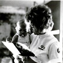Image of Karen Etchelis of Public Health Staff with one of her young patients