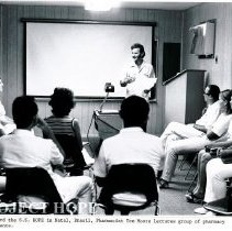 Image of Thomas Moore, pharmacist, addressing a group of students.