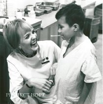 Image of Patty Sellers chatting with young patient and taking his temperature