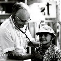 Image of Dr. Carl Fischer, pediatrician with a young patient.